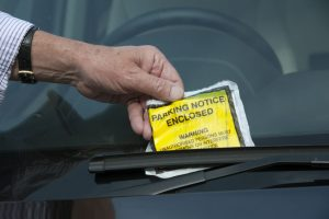 20623144 - man removing parking ticket from windscreen